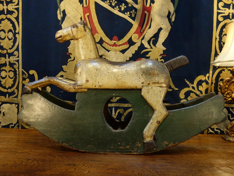 """18th century Baroque style handcrafted rocking horse. Delightful simplicity in carved and painted wood, circa 1760.  Measures: 48"""" L x 13"""" D x 31"""" H."""