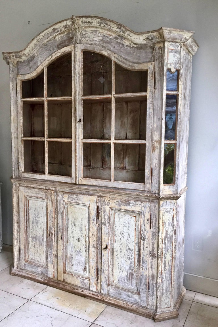 A very handsome 18th century French bookcase/vitrine cabinet in impressive scale with arched pediment cornice and panelled doors on three door cabinet base with bank of drawers inside of the middle section - all in time worn original patina. Here