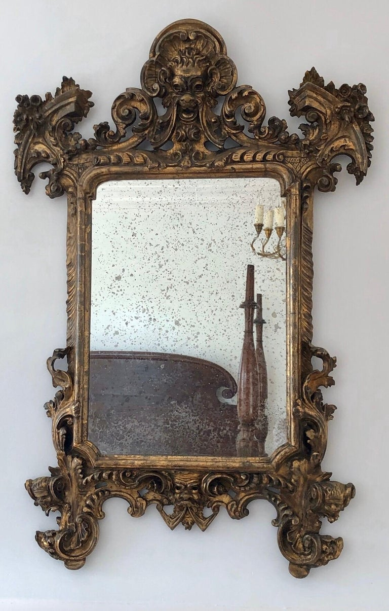 This 18th century Baroque giltwood Italian mirror has a theatrical face on the crest with swags flowing to the cornucopia corners. The bold frame has scrolls that are classically carved. The bottom rail also has a Theatrical Face. The mirror raises