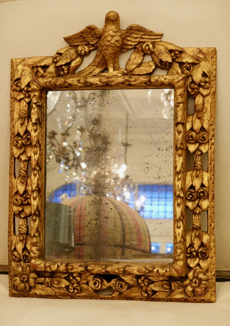 18th century Italian giltwood mirror with hand carved eagle, roses, leaves and other details. The carving around outer perimeter of the mirror to really highlight the details. Appears to have original mercury glass. Would make a very beautiful