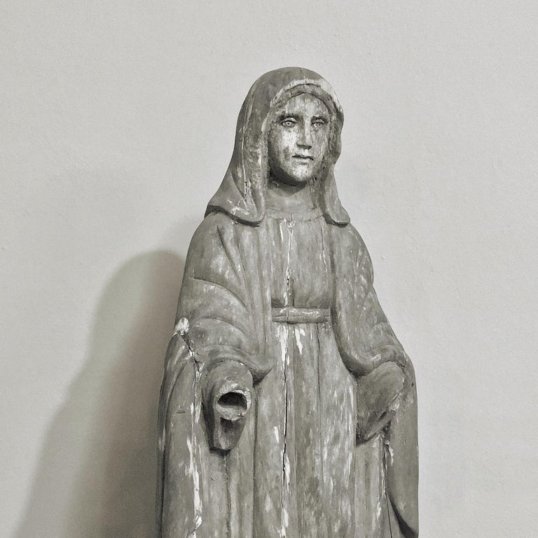 At once capturing the devotion and beauty of the Mother of Christ, this eloquent 18th century hand carved statue of The Madonna features her perched on a pedestal of a cloud, standing upon the sickle, which was a symbol of the Islamic faith with