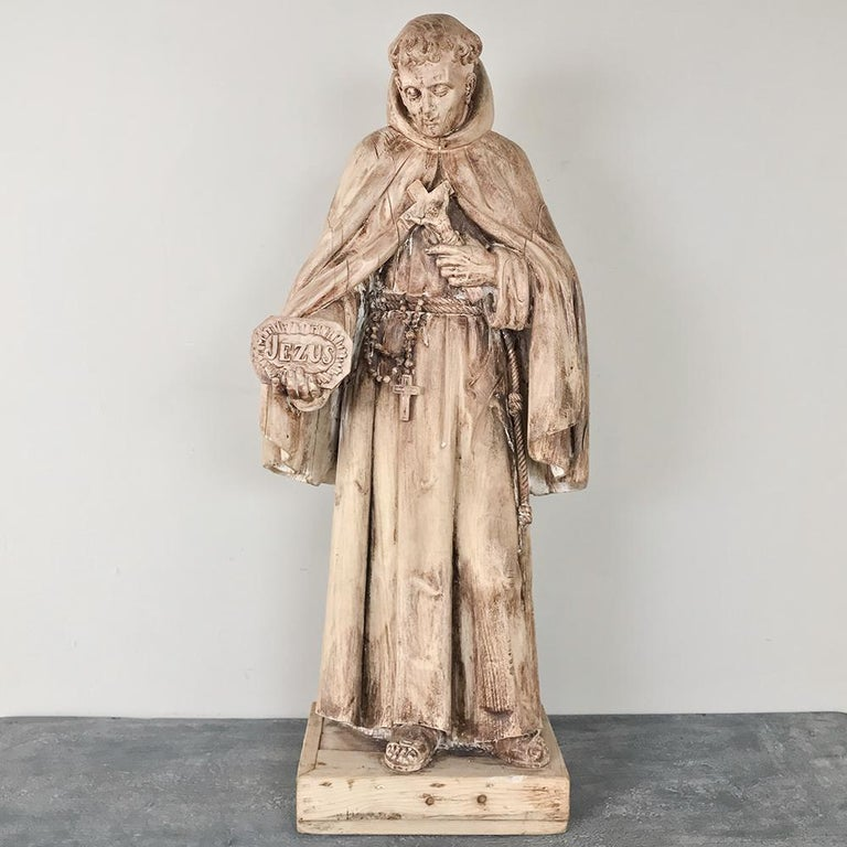 18th century carved wood statue of Saint has been carved with the figure in the raiment of a Monk holding a plaque with the name of Jesus inscribed into it. The classical pose, weathered finish, and medium size make this an especially appealing