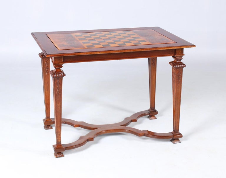 18th century chess and backgammon table  South Germany Walnut Louis XVI around 1780  Dimensions: H x W x D: 73 x 99 x 64 cm  Description: Tapered downward square legs with fine carvings. Cross-shaped curved central bar with thread