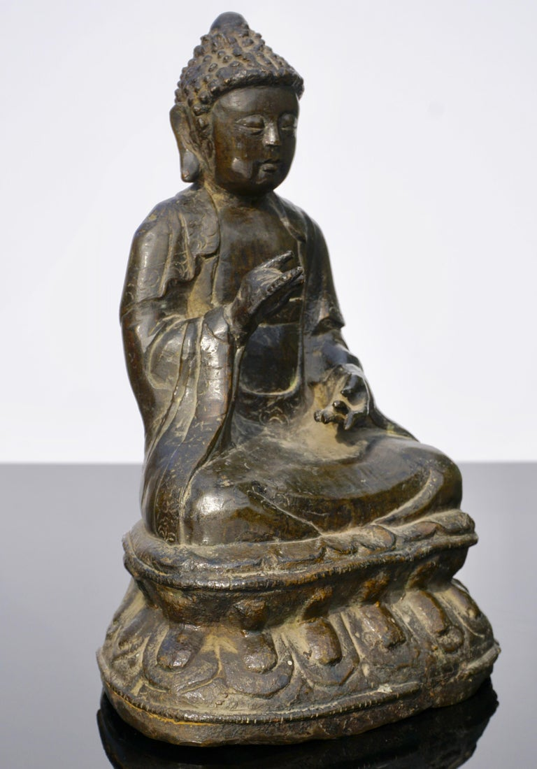 A 18th century or earlier Provincial large bronze figure of Buddha at 10 inches. His gaze downward in serenity his hands in abhisekana mudra seated on a double lotus. A nice older Buddha with limited detail, China, circa 1800.  Measures: Height 10