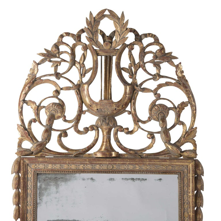 An exceptional mid-18th century French gilded and crested mirror in original condition.