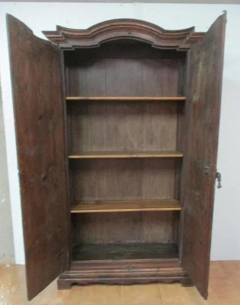 Grand 18th century Spanish armario or wardrobe armoire constructed from oak. Features a coffered case fronted by two large doors. This massive cabinet made in Spain features beautiful walnut grain and showcases the amazing craftsmanship. There is a