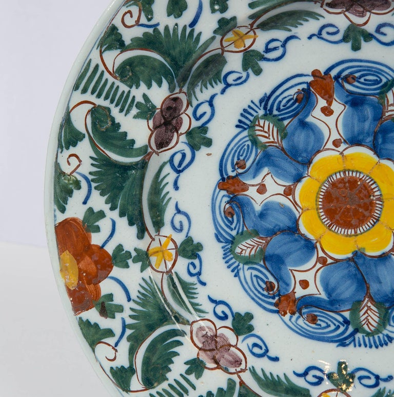 We are proud to offer this 18th century Dutch delft charger hand painted with a burst of polychrome colors: green, blue, orange, and yellow. The colors are painted over the glaze with the exception of the cobalt blue which is painted under the