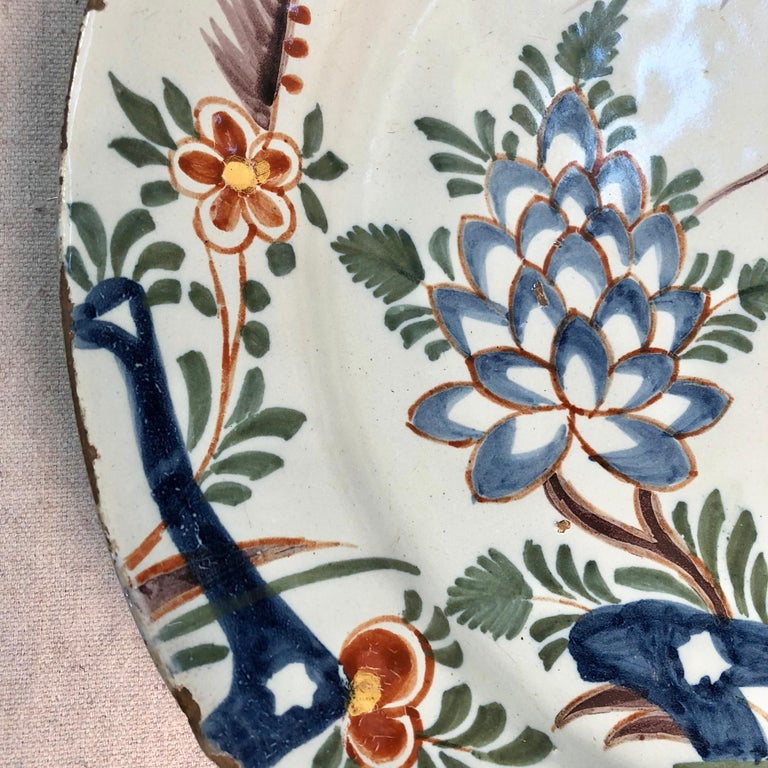 A wonderful and colorful Dutch delft charger, circa 1750. Basket with flowers.