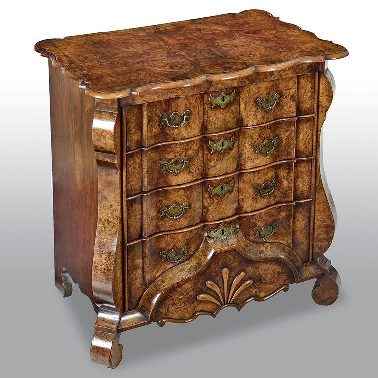 An exceptionally fine mid-18th century Dutch burr walnut commode, with superb original colour and patina, with quarter veneered rectangular serpentine shaped top above four waved graduated drawers with original brass handles, shaped apron, on