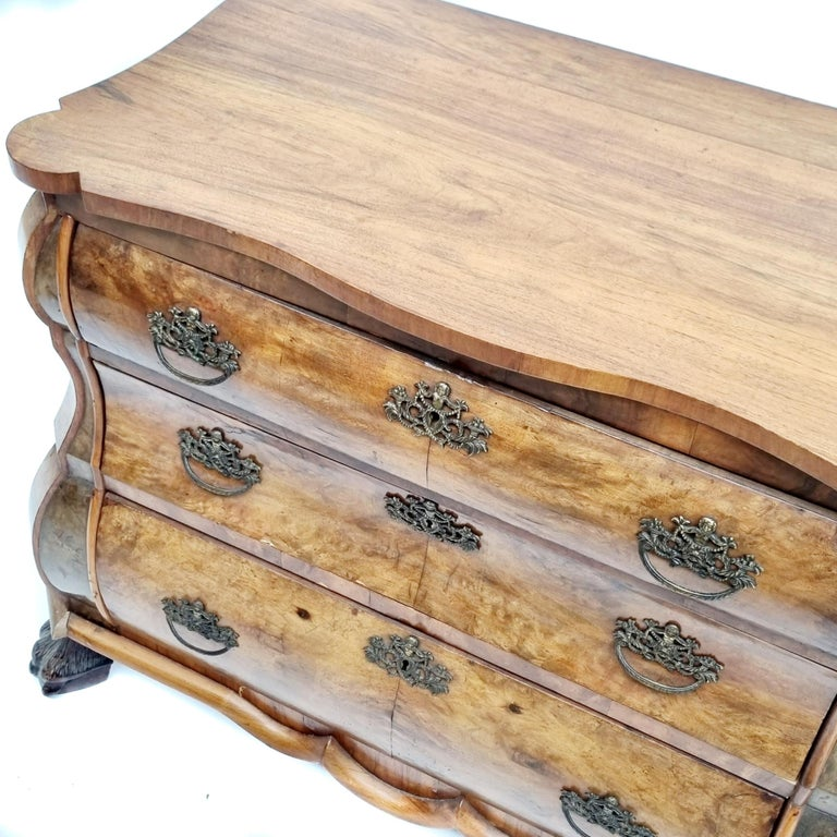 Dutch chest of 3 drawers with claw feet from the 19th century in walnut burl veneer. Good example of a 19th century Dutch design bombe shaped commode.Fitted with 3 drawers and ornate handles. Standing on 4 lion paw carved feet. Overall good vintage
