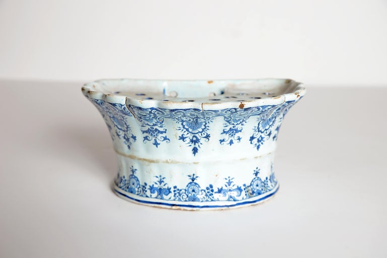 An 18th century Dutch delft hanging (wall mounted / wall pocket) bough pot of D-shaped fluted form. The bough pot features traditional hand painted blue and white floral decorations. Holes and water well on the top.