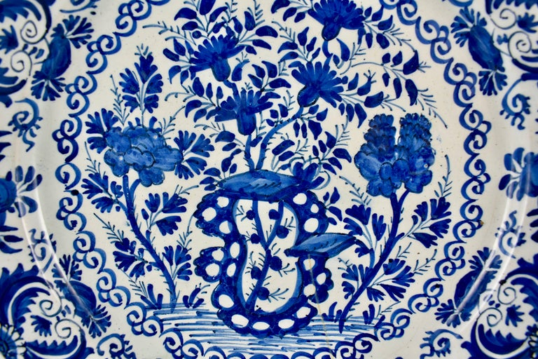 An 18th century Dutch delft, tin-glazed earthenware deep charger, inspired by Chinese export porcelain and hand painted in a heavy cobalt blue chinoiserie style overall floral pattern. A stylized border of an alternating floral like pattern is edged