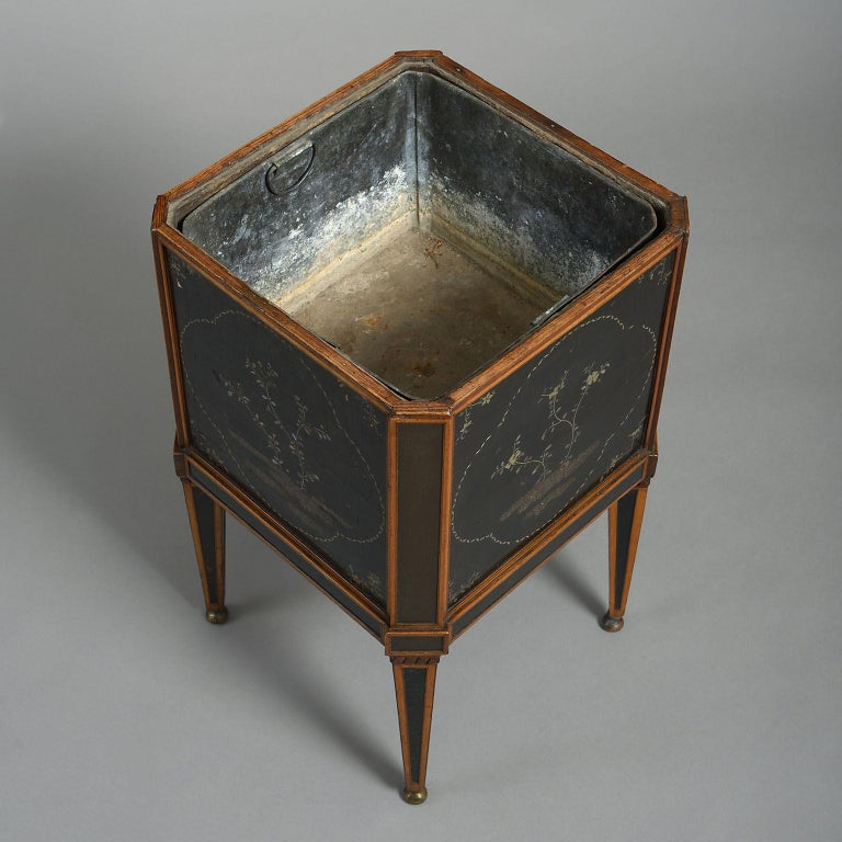 The square form with canted corners, mounted with oriental lacquer panels, probably from a tea-box, and raised on angled square tapering legs, also inset with lacquer panels and standing on brass ball feet.