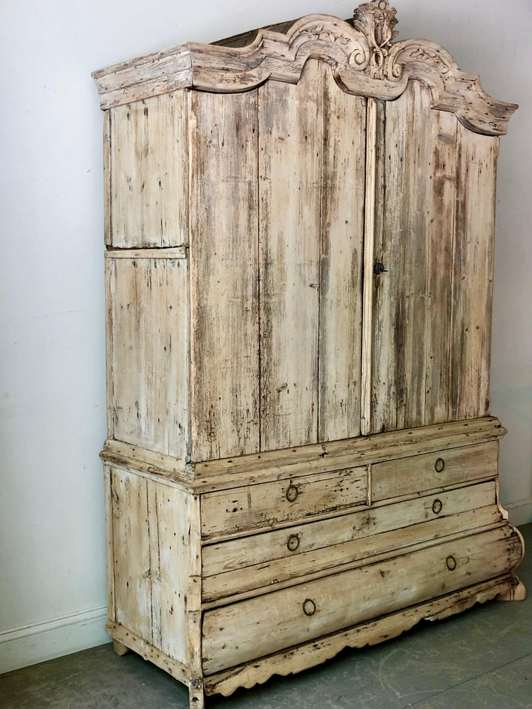 18th century Dutch beached oak two-piece cabinet with bonnet shaped pediment with delicate flower carvings,. The upper cabinet sits atop four bombé drawers with calloped skirt and carved feet.