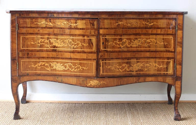 A large and elegant late 18th century Dutch serpentine front two-door cabinet with extensive marquetry inlay in exotic woods. The two cabinet doors reveal three shelves ideal for linen storage. The cabinet rests on cabriole legs terminating in