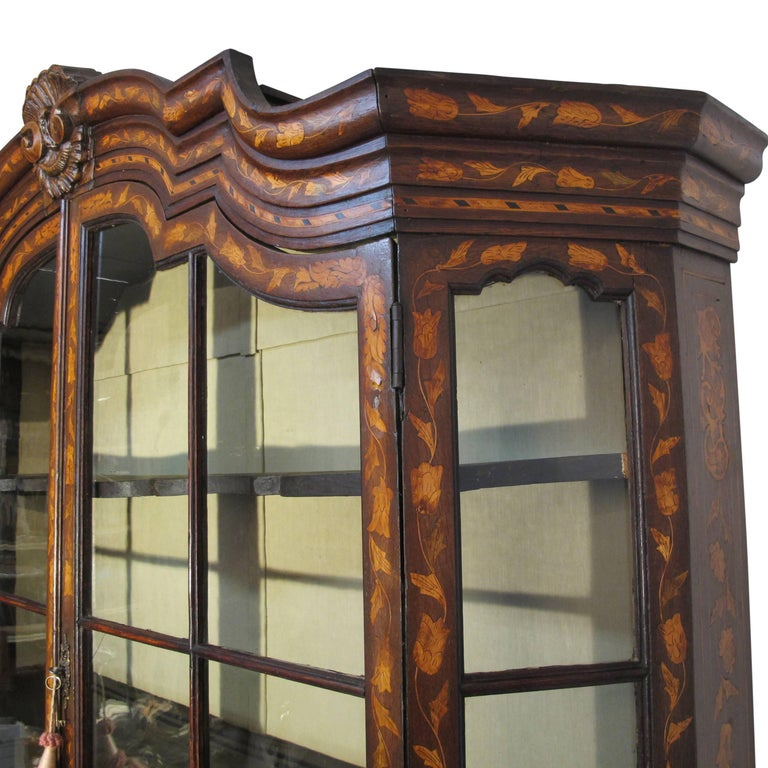 A beautiful example of an early 18th century Dutch cabinet. Walnut with fruitwood inlay marquetry design of leaves, flowers and urns. Having its original shelves, original hardware, and most of the original glass. Recently re-lined interior in silk