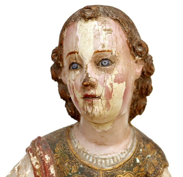 18th century ecclesiastical carved Arcangel sculpture, gilt and polychromed  Offered for sale is a late 18th century religious carving of an Arcangel with the remnants of the gilt and polychromed finish. The figure retains the inset glass eyes.