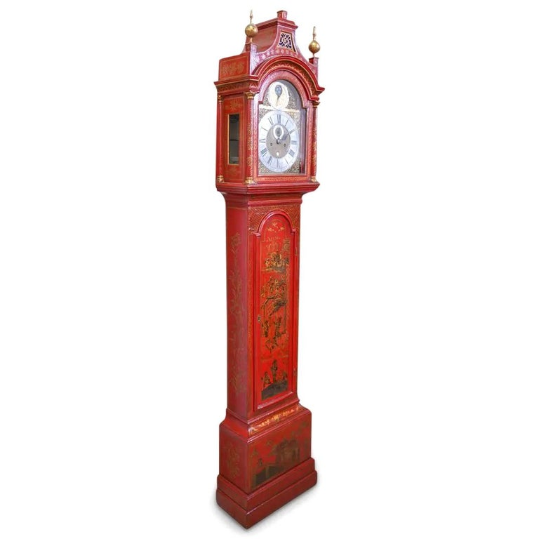 An 18th century English Chinoiserie grandfather clock or longcase clock. Features a red lacquered wood case with figural and village decorations. Clock housed in architectural arched case with gilt details and sphere finials. Clock face designed