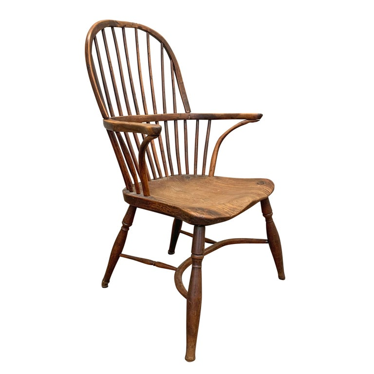 A wonderful late 18th century English elm and yew wood Windsor chair with a hoop back, out-turned arms supported by inverted stretchers, turned legs connected by a bentwood stretcher. The seat is one piece of wood with a beautiful patina.