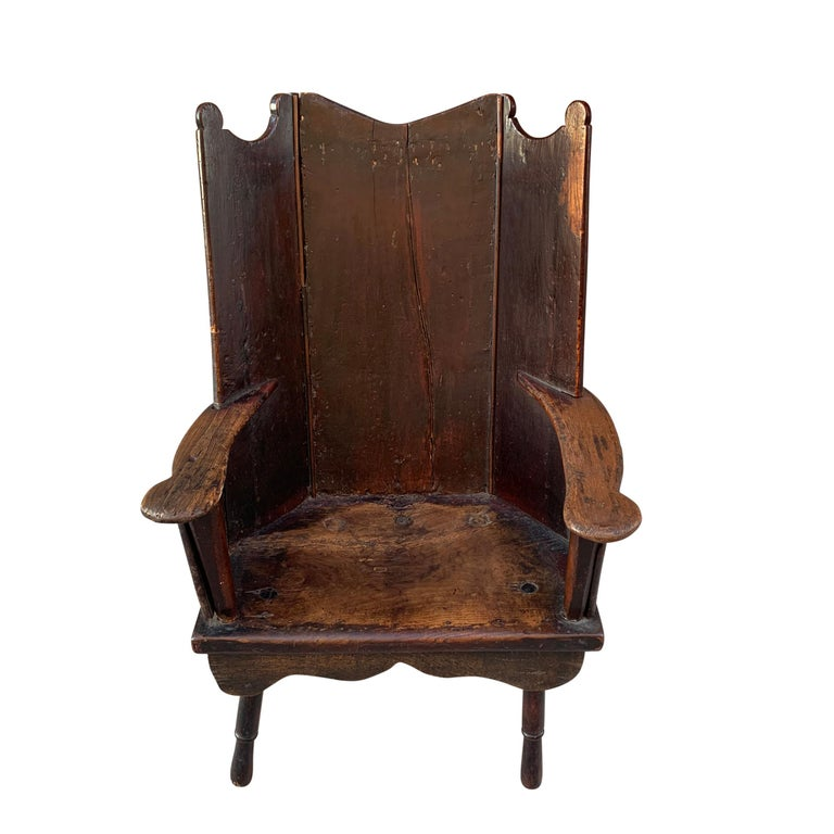 An extraordinary 18th century English oak wingback chair having a back constructed of three oak panels with scalloped top, and straight flat arms with rounded ends, through turned front legs and more recent back legs. The seat has a fantastic patina