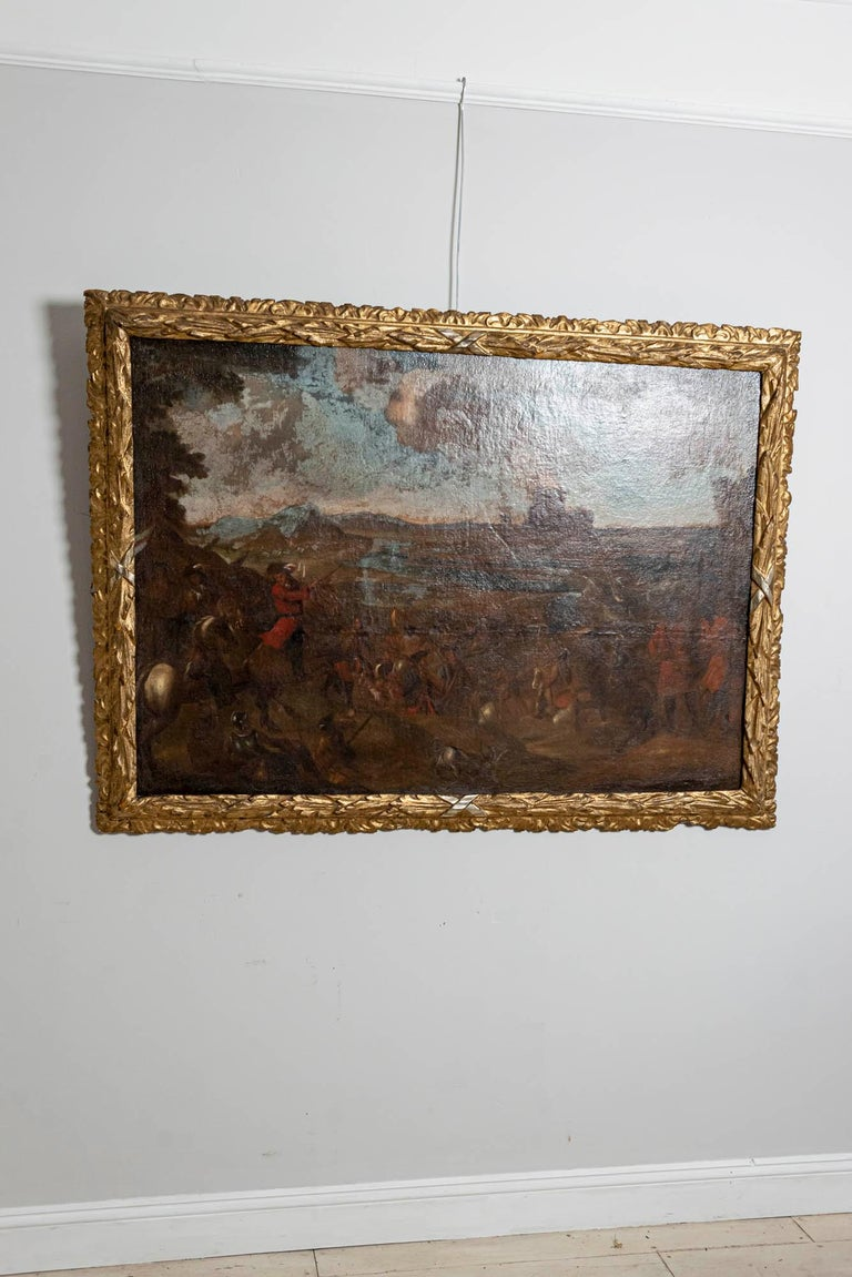 Framed oil painting of a battle scene in Europe, circa 18th century. The painting has an impressive carved gilt frame. Over the years the painting has had some paint loss and has been restored and retouched in the past.  The artist and the scene