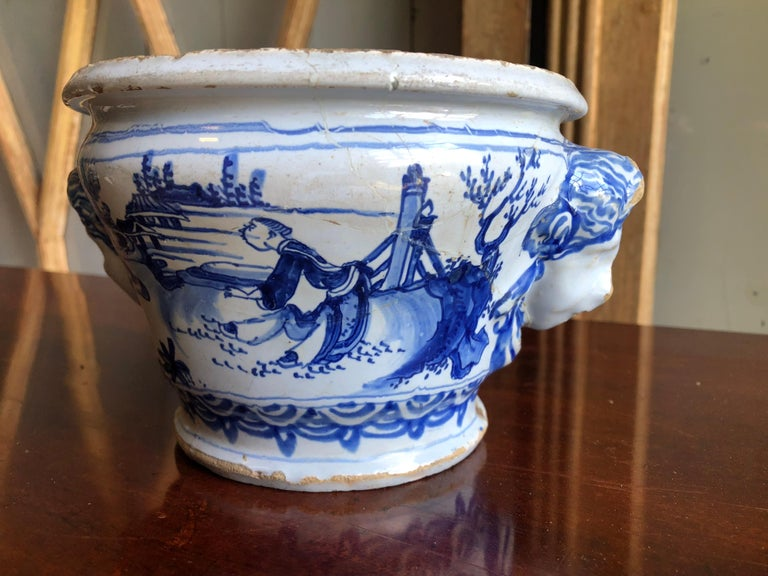 An 18th century French faience cachepot from Nevers, with blue chinoiserie decoration and masks on each side, circa 1750.