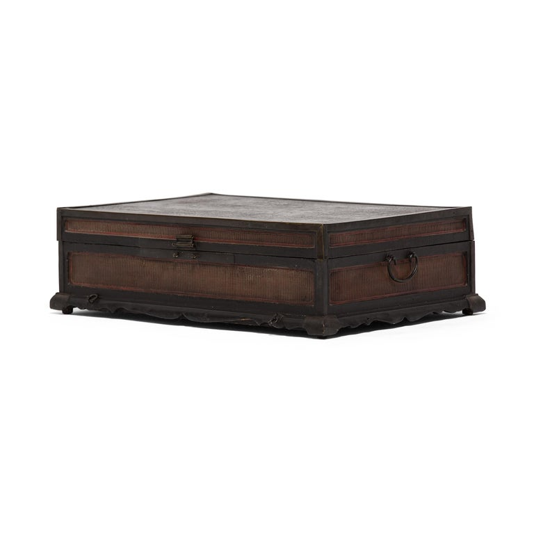 This 18th-19th century finely woven trunk was originally used to safely store painted scrolls. A skilled artisan painstakingly wove thin-as-hair reeds to cover each of the side panels, protected and reinforced by original brass corner mounts. The