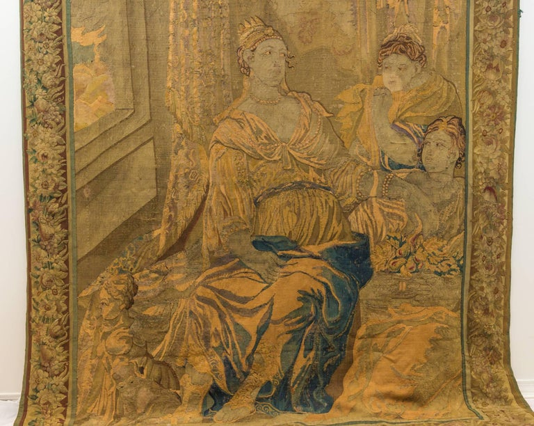 Handwoven wool tapestry mid-late 18th century Brussels figural scene depicting three females in lavishly decorated sitting room with open window. Crowned Queen dressed in pearl necklaces and bracelets, draped gown and detailed sandals. Two ladies in