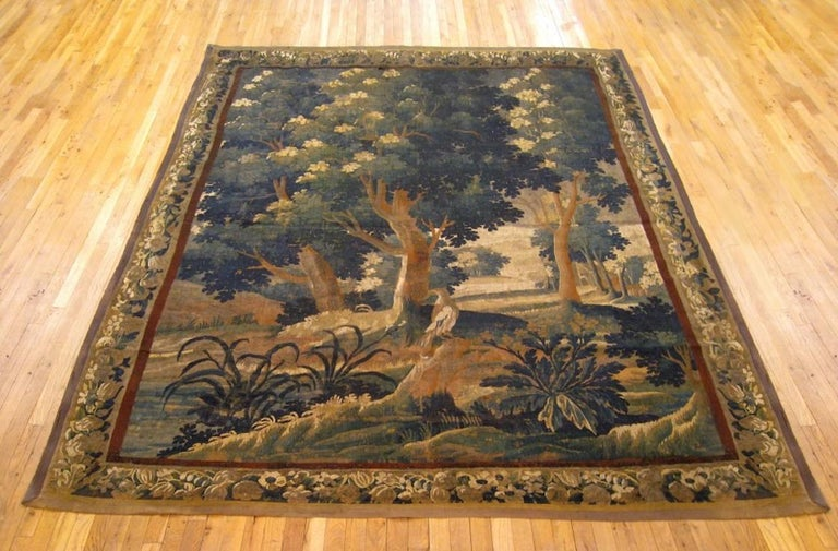 """A Flemish verdure landscape tapestry from the 18th century, depicting a bird in a verdant scene between large trees and various foliage in front of a lake. Enclosed within a fruiting and flowering border. Wool with silk inlay. Measures: 9'10"""" H x"""