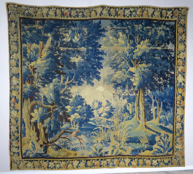 18th century Flemish Verdure tapestry depicting birds and a beautiful scene of foliage and trees throughout. The tapestry is handmade in both silk and wool with vibrant hues of greens, blues, gold and more. Good overall condition with areas of
