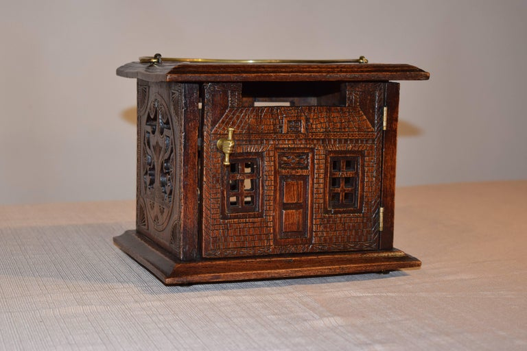 18th century English oak foot warmer with pierced and carved decoration on all sides. The top has a molded edge and is banded with carving surrounding a central pierced medallion. The front looks like a house with a front entrance and hand a scroll