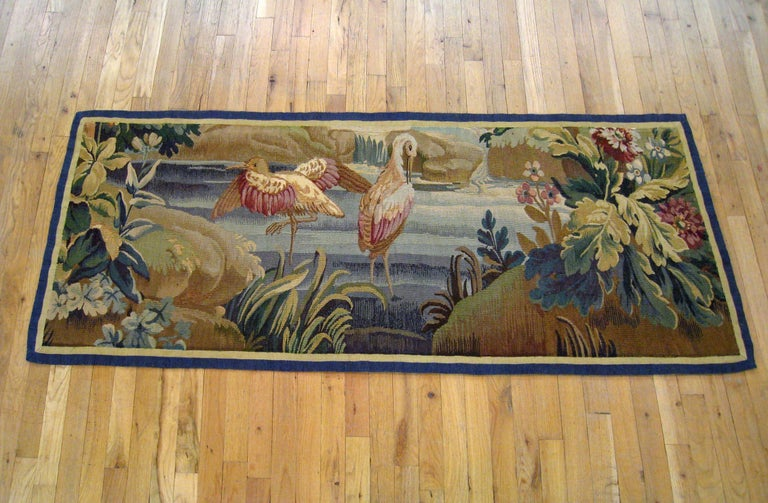 A French Aubusson verdure landscape tapestry from the 18th century, with two birds in a stream by grassy banks covered with acanthus plants and flowers. Enclosed within a pair of narrow monochromatic borders. The backing features a Fleur de Lis