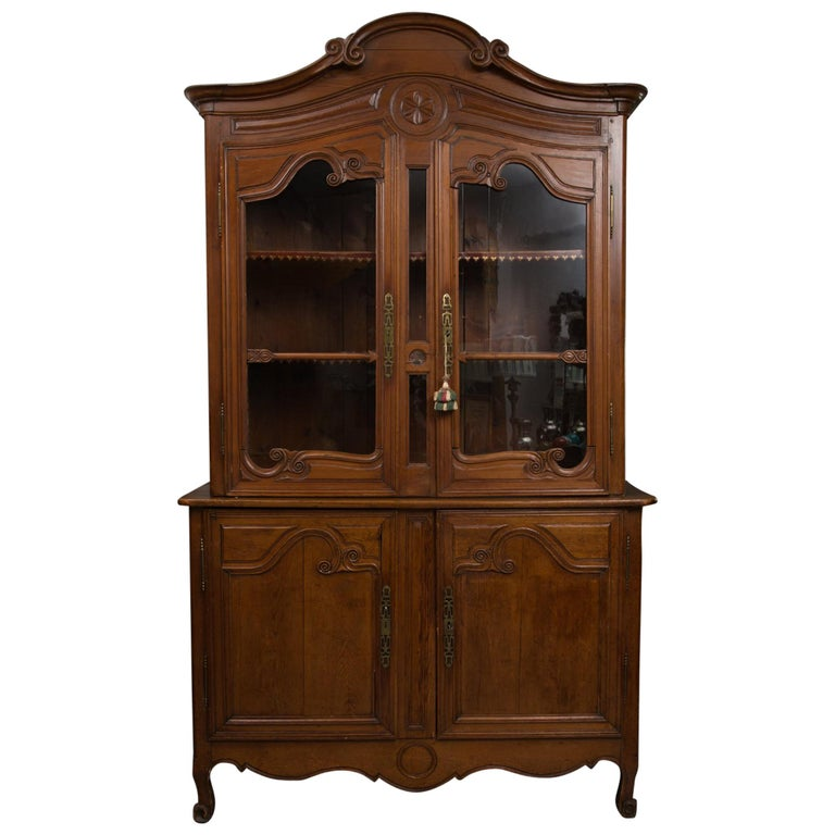 This is an early French Louis XV provincial cherrywood buffet a deluxe corps with an arched cornice over a carved conforming frieze above two glazed doors situated on a bottom section with a pair of carved paneled cabinet doors over a carved, shaped