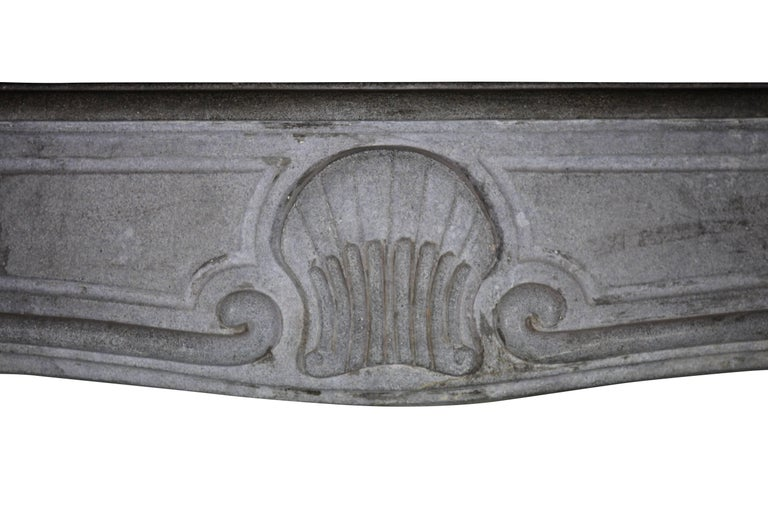 A bicolor bleu-grey French Burgundy hard limestone fireplace surround with little remaining of patin and a rustic twist. It has a lovely shell shaped carving on the front typing the Regency to Louis XV period.  Measures: 153 cm EW 60,24