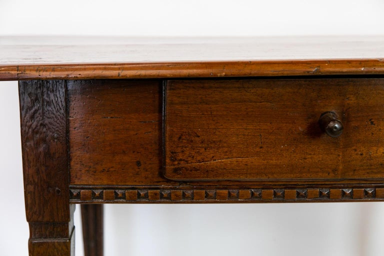 18th century French fruitwood work table, has a carved apron, and its four legs are fluted on all four sides. There is a small companion drawer on the right side. The carved wooden knob is original.