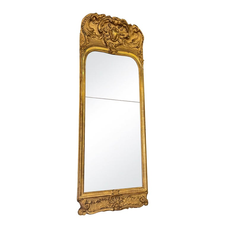 An antique French Rocaille décor gilded wood mirror with facet, in good condition. The mirrored glass is original. The mirror represents the Rococo time period. Wear consistent with age and use, Circa 1760, France.