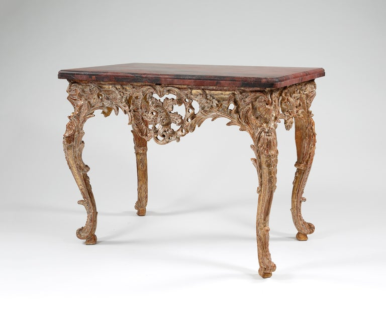 A stunning French Rococo giltwood console table with later rectangular marble top. The frieze is centered by a large carved cartouche. The base is finely carved with foliate decoration throughout.