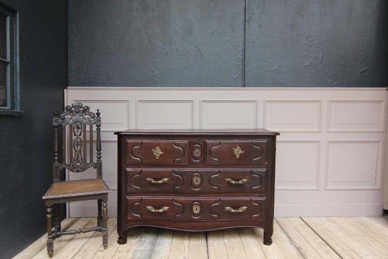 """A mid-18th century French Louis XIV chest of drawers from Paris. Stamped """"JME H. Hansen"""" for Hubert Hansen (master from 1747, died 1756). Slightly trapezoidal, double-curved body with volute feet on the front and protruding profiled cover plate."""