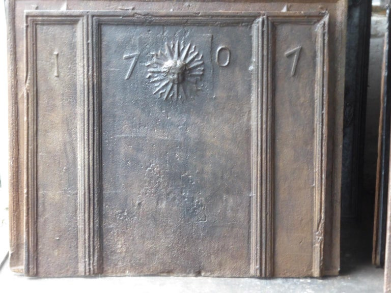 18th century French Louis XIV fireback. The sun symbolizes King Louis XIV of France who was called the Sun King.   The fireback is made of cast iron and has a natural brown patina. Upon request it can be made pewter / black. The fireback is in a
