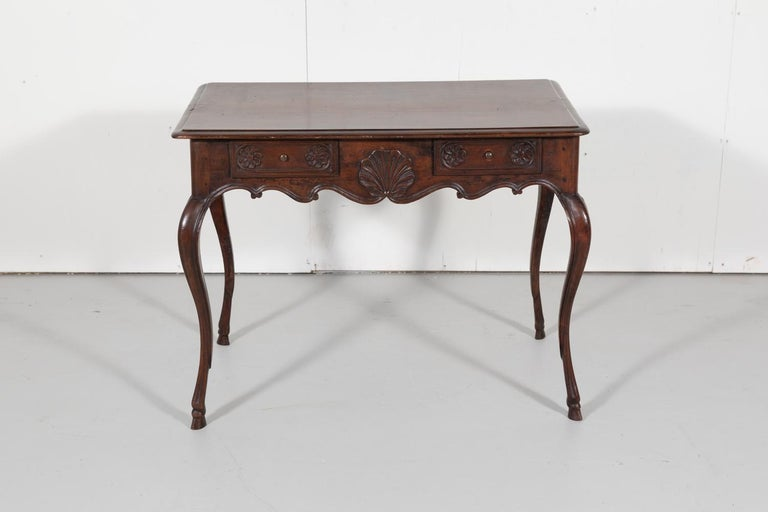 Fine 18th century French Louis XV period side table or ladies desk handcrafted in solid French walnut by talented artisans near Lyon. This richly carved French table features a rectangular top with moulded edges and rounded corners sitting above an