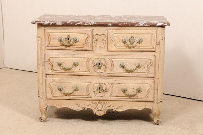 A French period 18th century finely carved, marble top commode. This French period Louis XV Provincial commode, circa 1750-1760, features two smaller drawers at top, divided with plaque at center, over two full length drawers, each drawer has