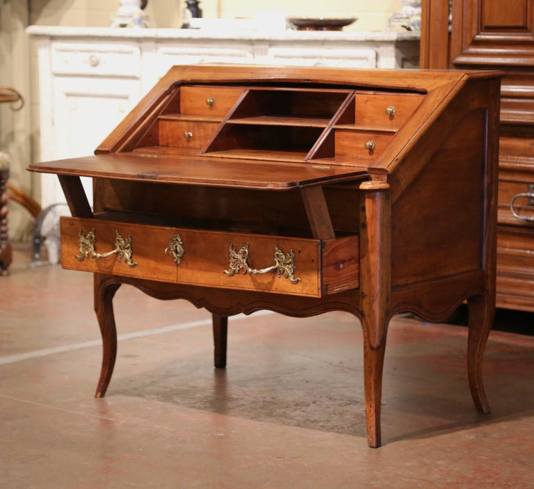 Carved in southern France, circa 1760, the fold out secretary is both stylish and functional; the elegant writing desk crafted from solid walnut, stands on cabriole legs over a scalloped apron and dressed with bombe drawer across the front