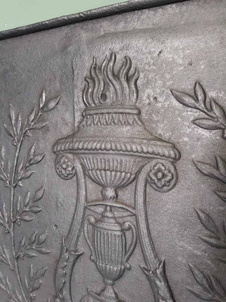 Antique French cast-iron Louis XVI hob with typical relief image from that time of a vase with flames and standing on claw feet, late 18th century.  The measurements are, Depth 2 cm/ 0.7 inch. Width 50 cm/ 19.6 inch. Height 50.5 cm/ 19.8 inch.