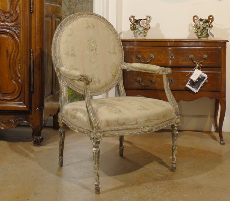 A French Louis XVI period painted and carved wooden fauteuil from the late 18th century, with oval back, floral fabric and distressed finish. Born in France during the reign of King louis XVI, this armchair features an oval back, adorned with