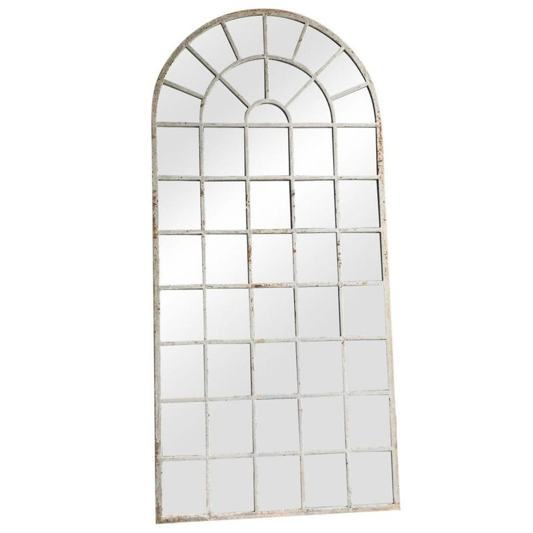 Late 18th Century, a very tall, antique Orangerie wall mirror with an arched top, in good condition. The structure has a cast iron antique frame and newly inserted mirrored panels. The antique wall décor represents the Renaissance Revival time