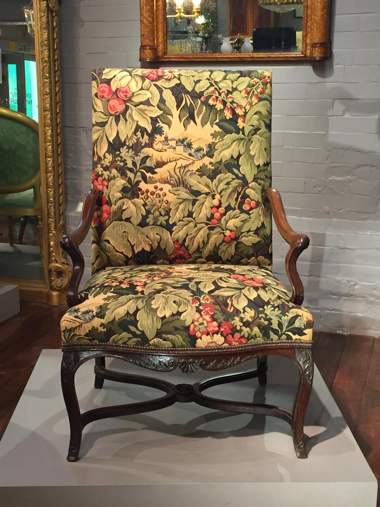 A good mid-18th century French oak high back open armchair. The upholstered seat and back with shaped arms and apron standing on fine cabriole legs joined with cross stretcher and central carved boss. The apron carved on all sides with central shell