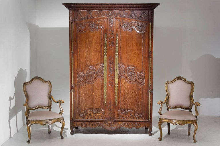Excellent quality, very nice model, 18th century wonderfully carved French oak armoire with fantastic original brass metalwork and three massive door hinges each side.