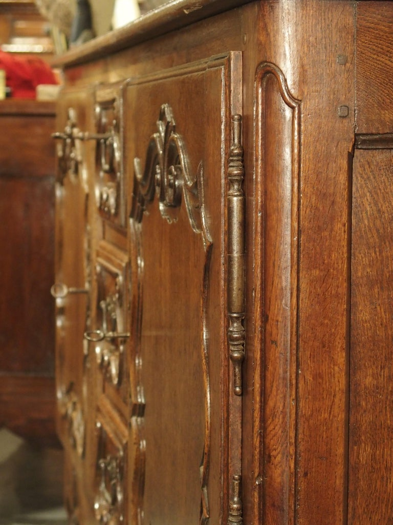Hand-carved in France during the 1700's, this amazing oak buffet has two doors on iron hinges that are separated by three vertically stacked drawers. This orientation is often found in buffets produced in the Lorraine region, which borders Germany,