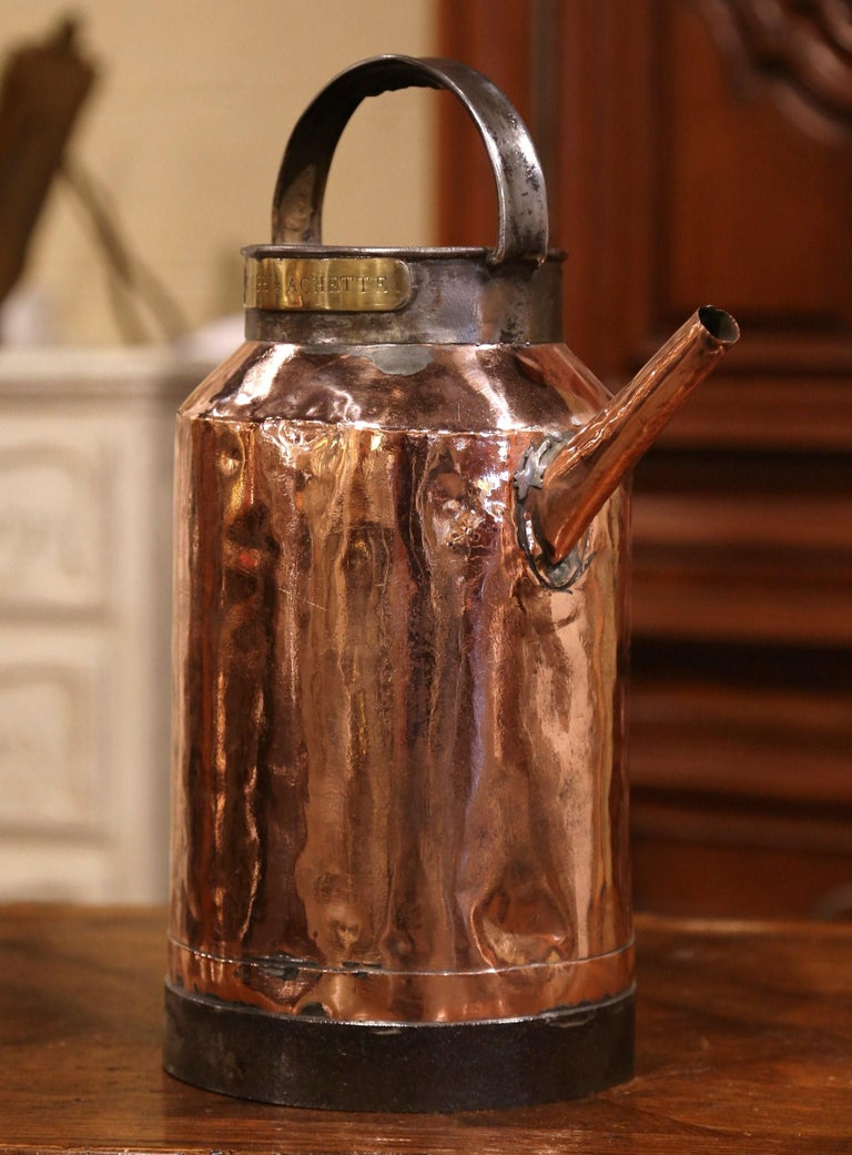 Water your plants elegantly with this antique copper and iron watering can, crafted in France, circa 1780, the can stands on a forged iron round base, the water piece features a top and a side handles, embellished with a pouring spout. It is further