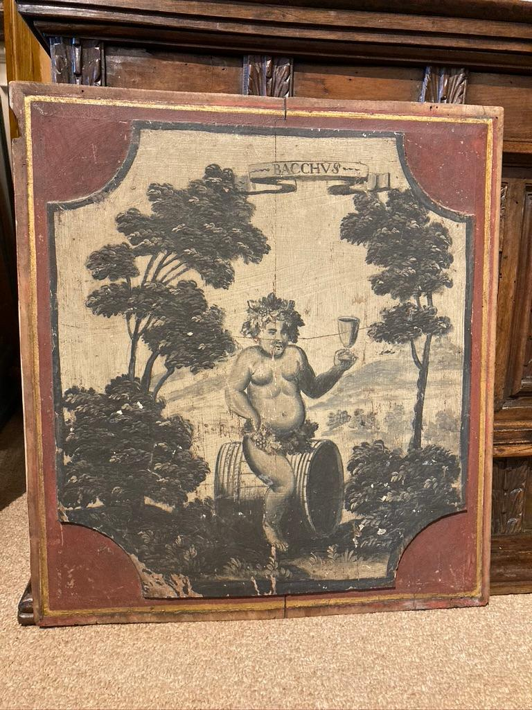 An amusing French Provincial painted panel showing a chubby Bacchus, the Greek god of wine, astride a wine barrel, naked except for grapes and wine leaves around his waist, holding a goblet aloft. The raised cartouche painted in grisaille technique,